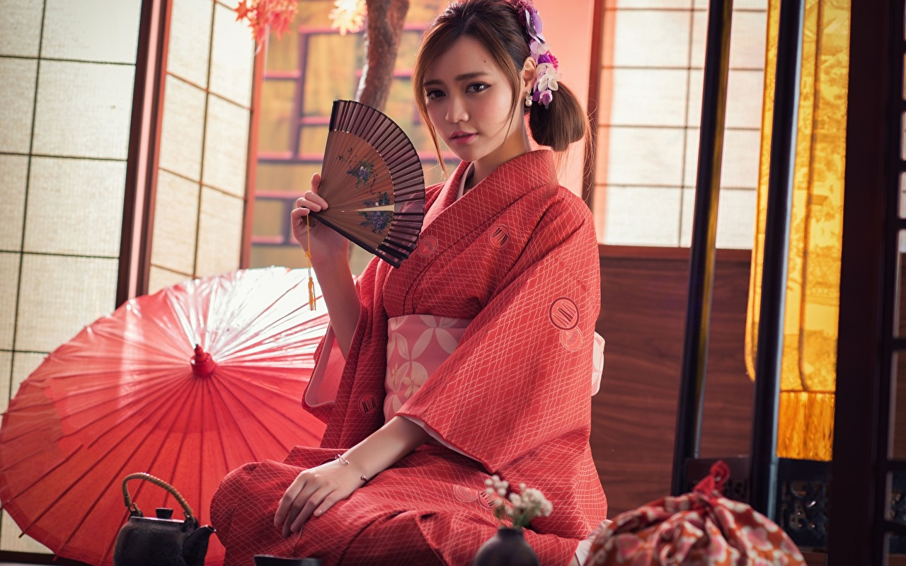 Desktop Wallpapers Brown haired Japanese Hand fan Kimono young woman Asian Hands Sitting Staring Girls female Asiatic sit Glance
