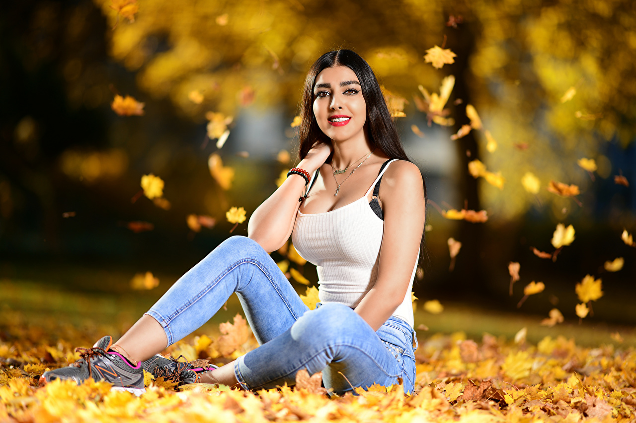 Picture Leaf Brunette girl Smile Bokeh Autumn young woman Jeans Singlet sit Staring Foliage blurred background Girls female Sleeveless shirt Sitting Glance