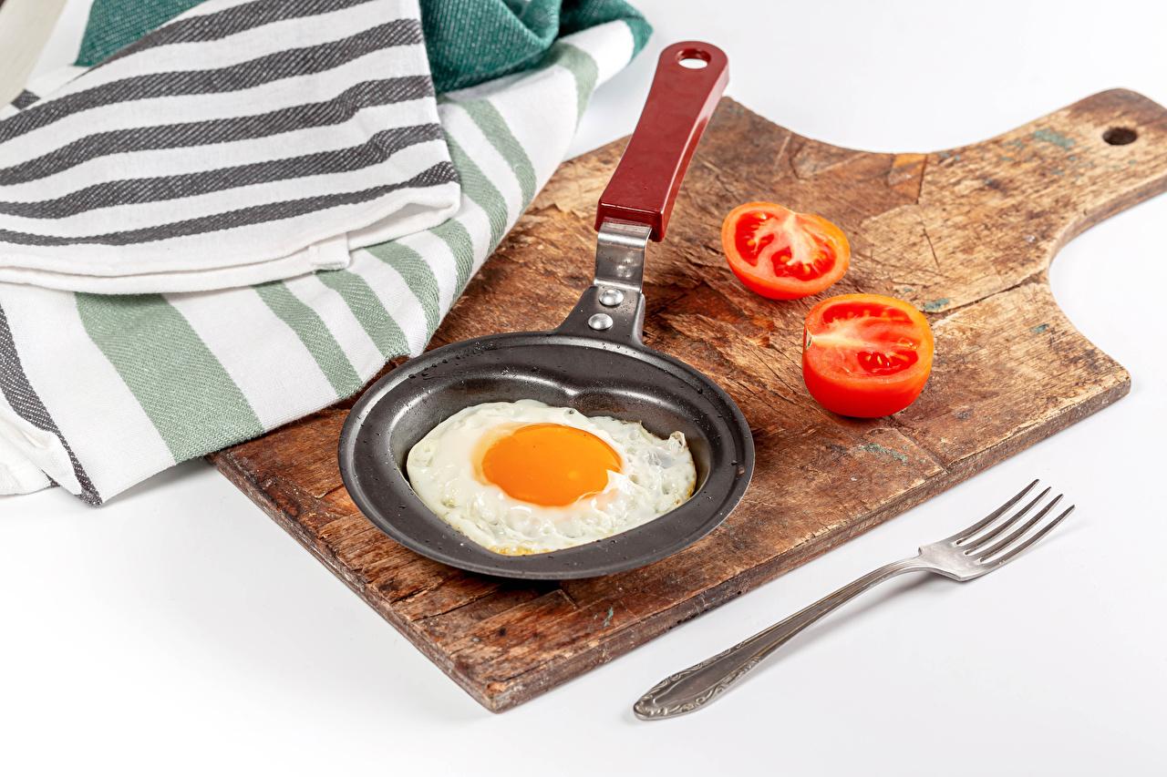 Fotos von Spiegelei Tomaten Pfanne Essgabel das Essen Schneidebrett Weißer hintergrund Tomate Bratpfanne Gabel Lebensmittel