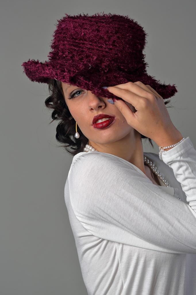 Bilder Brünette Schminke Pose Der Hut Mädchens Hand Starren Grauer Hintergrund  für Handy Make Up posiert junge frau junge Frauen Blick