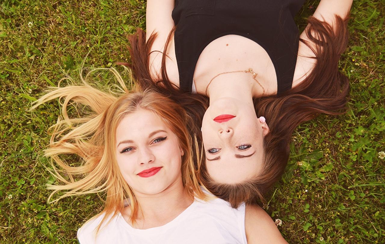 Foto Braunhaarige Blond Mädchen Liegt Zwei junge Frauen Gras Von oben Blick Blondine Braune Haare ruhen Liegen hinlegen 2 Mädchens junge frau Starren