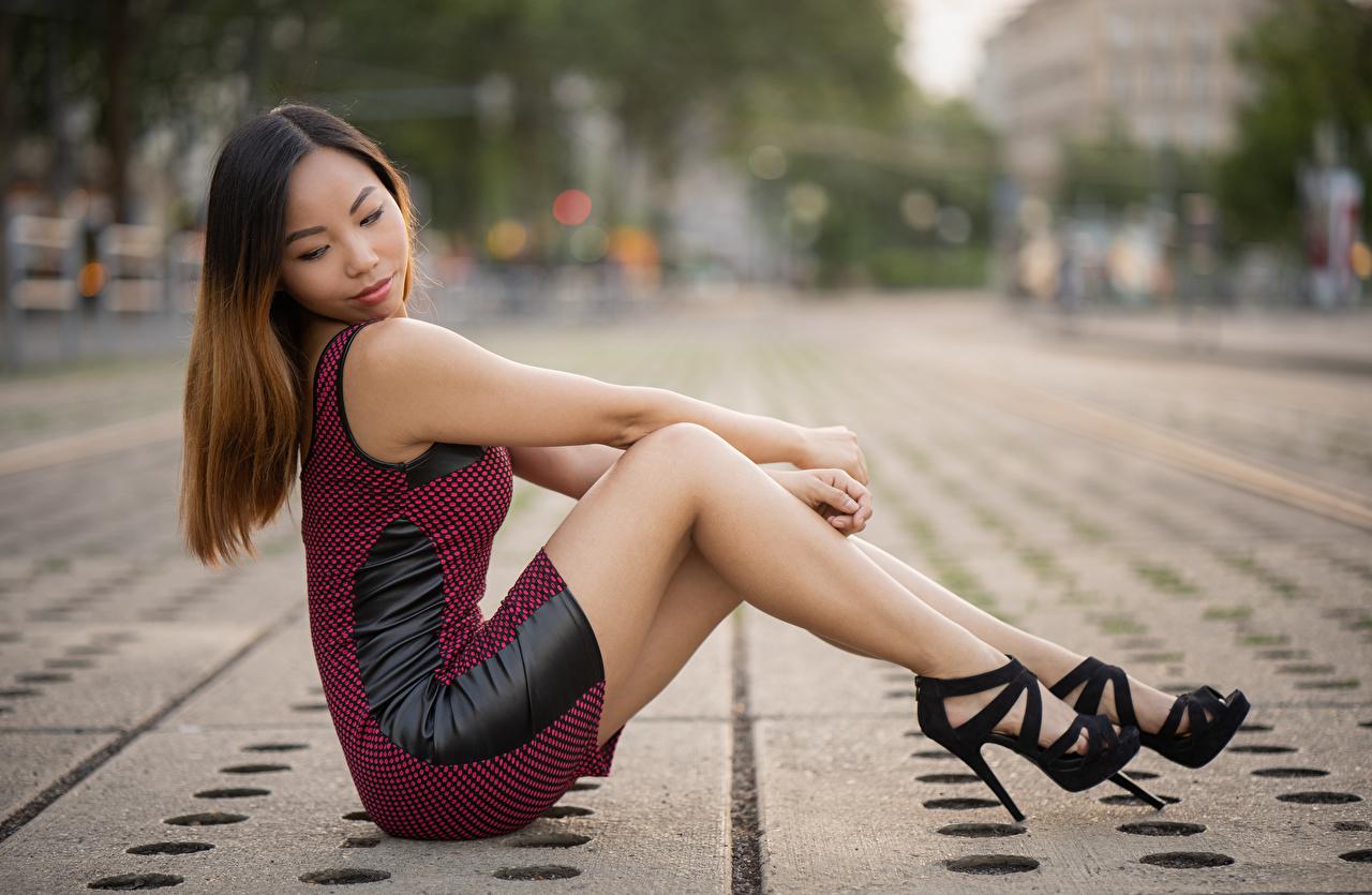 Bilder Braunhaarige unscharfer Hintergrund Mädchens Bein Asiaten Hand sitzt Seitlich Kleid Stöckelschuh Braune Haare Bokeh junge frau junge Frauen Asiatische asiatisches sitzen Sitzend High Heels