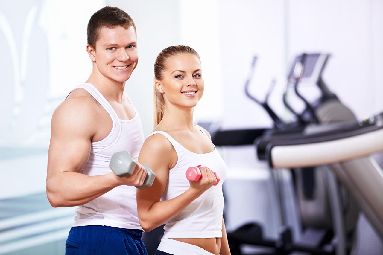 Fotos von Mann Lächeln Fitness 2 Hanteln Mädchens sportliches Unterhemd Zwei Sport Hantel junge frau junge Frauen