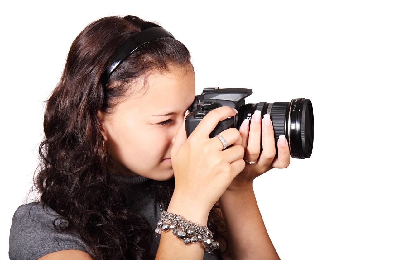 Desktop Hintergrundbilder Braunhaarige Fotoapparat Photograph junge frau Hand Weißer hintergrund Braune Haare Fotograf Mädchens junge Frauen