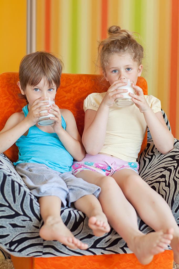 Fotos Milch Kleine Mädchen Junge Kinder Zwei Trinkglas Sitzend Blick jungen 2 sitzt sitzen Starren