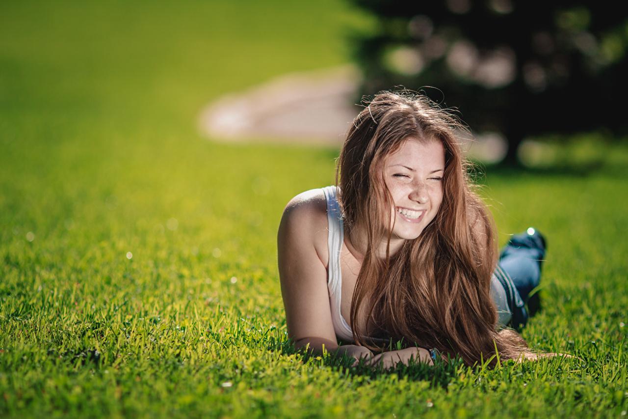 Fotos von Braunhaarige Lächeln ruhen Bokeh Süß junge frau Gras Braune Haare Liegt Liegen hinlegen unscharfer Hintergrund nett süße süßes süßer niedlich Mädchens junge Frauen