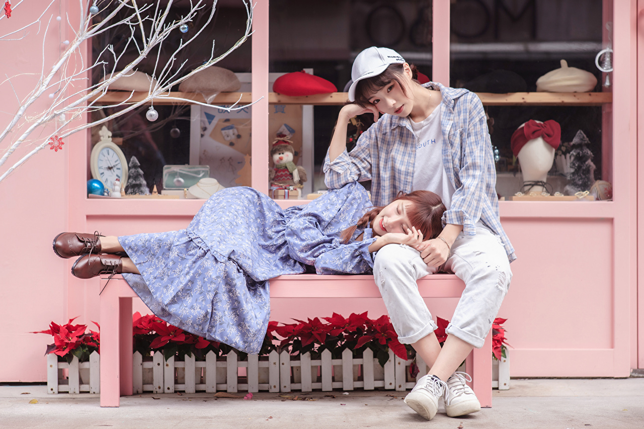 Desktop Wallpapers Lying down Two young woman Formal shirt Jeans Asiatic Bench Sitting Staring Baseball cap frock laying esting 2 Girls female Asian sit Glance gown Dress