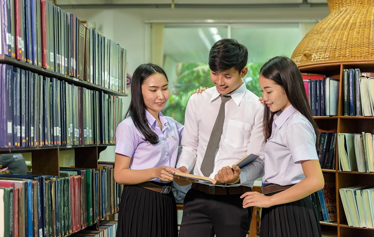 Fotos Brünette weibliche studenten Mann Bibliothek Krawatte Mädchens Asiatische Buch Drei 3 Studentin junge frau junge Frauen Asiaten asiatisches Bücher