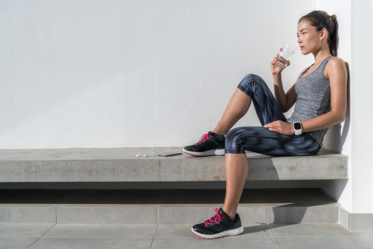 Bilder von Trinkt Wasser Fitness Ruhen Sport junge frau Trinkglas Unterhemd sitzen Erholung ausruhen Mädchens sportliches junge Frauen sitzt Sitzend