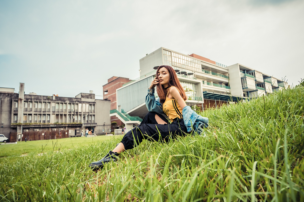 Image Girls Asiatic Sleeveless shirt Grass Sitting pants Glance female young woman Asian Singlet sit Staring Trousers