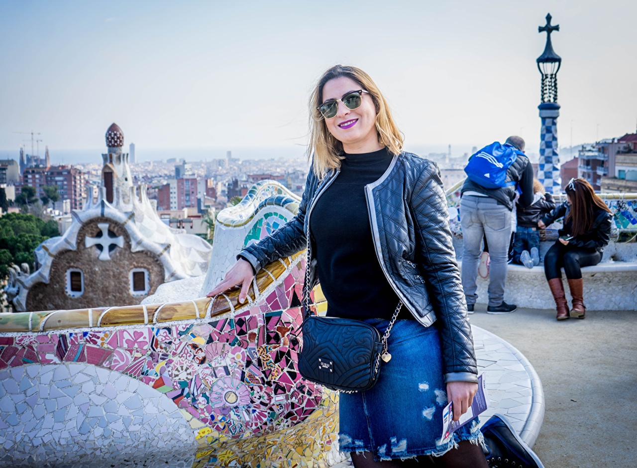Image Barcelona traveler Spain Tourism Blonde girl Smile Park Guel Jacket park Handbag eyeglasses Cities Tourist Parks purse Glasses