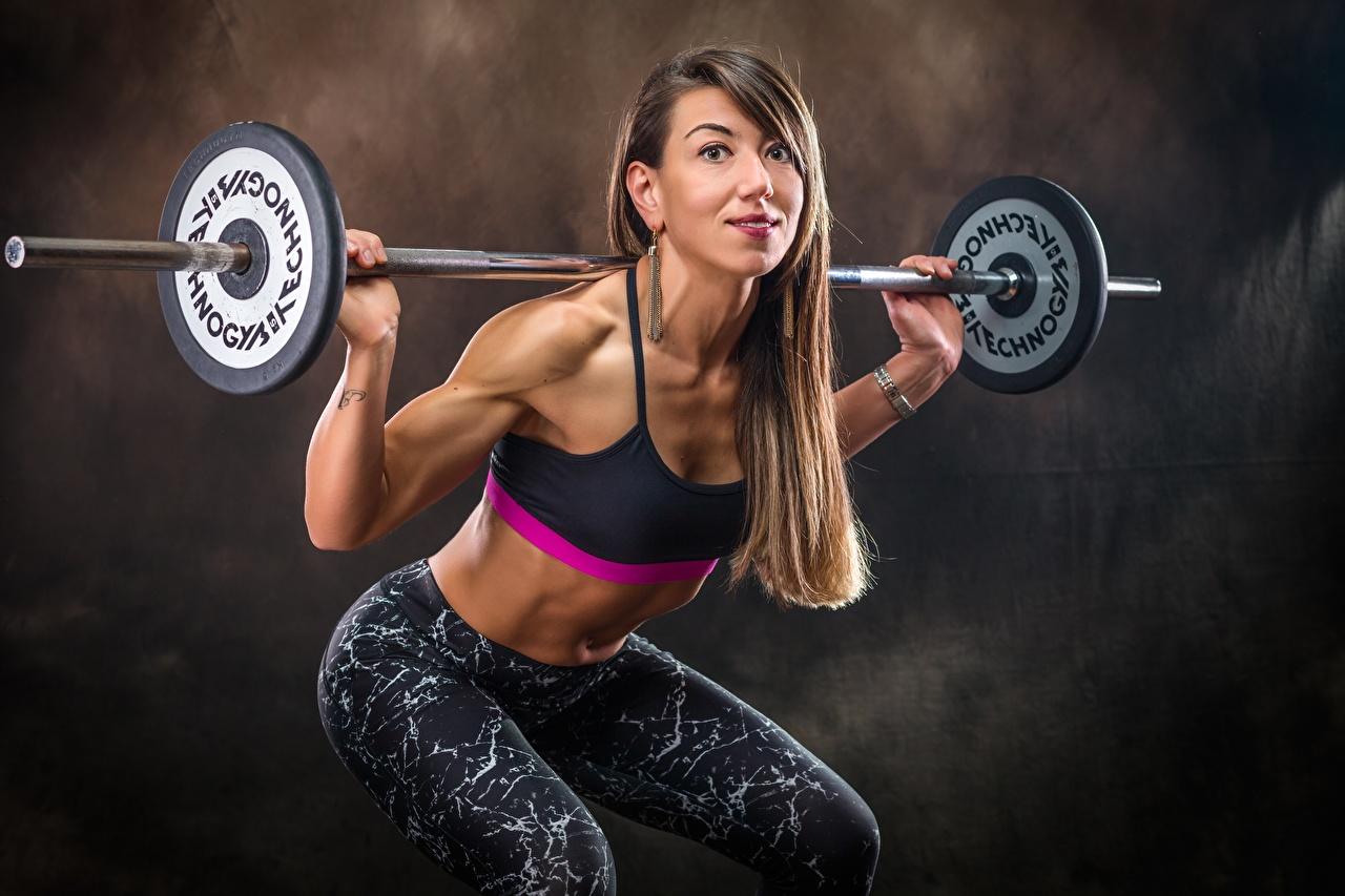 Bilder von Braune Haare Trainieren Kniebeugen posiert Fitness junge frau sportliches Hantelstange Hand Blick Braunhaarige Körperliche Aktivität hockt Kauert Pose Sport Mädchens junge Frauen Starren