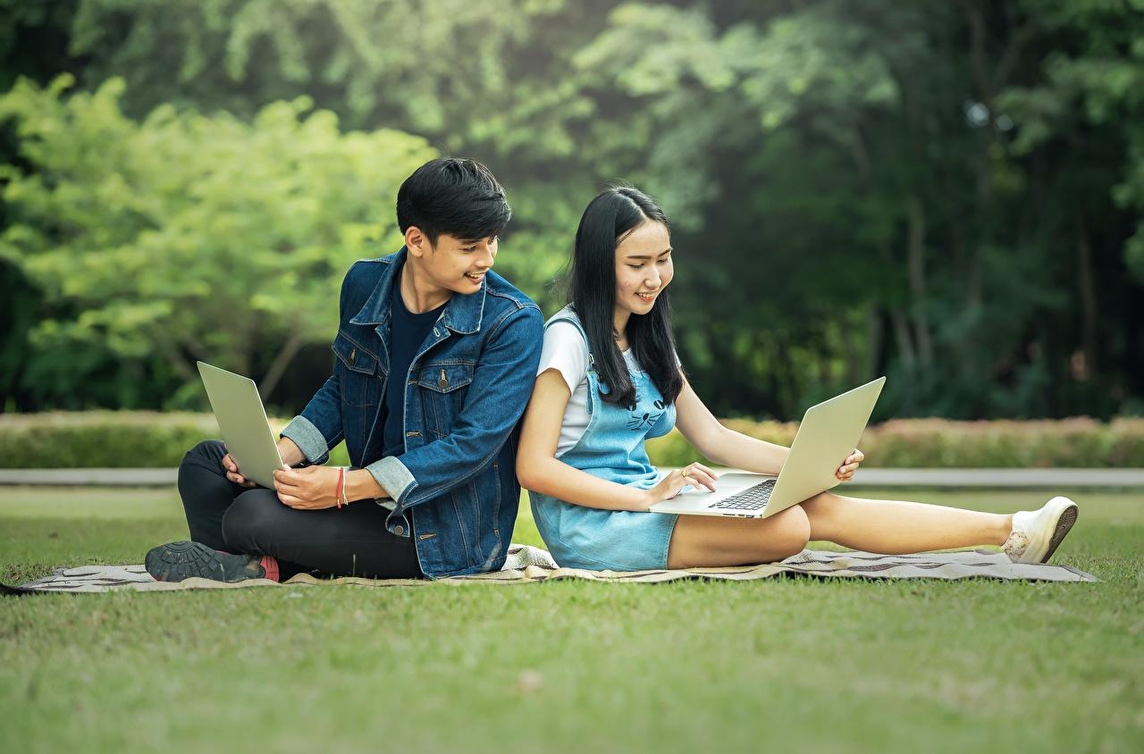 Photos Laptops Brunette girl Female students Men Girls Asian Sitting Man female young woman Asiatic sit