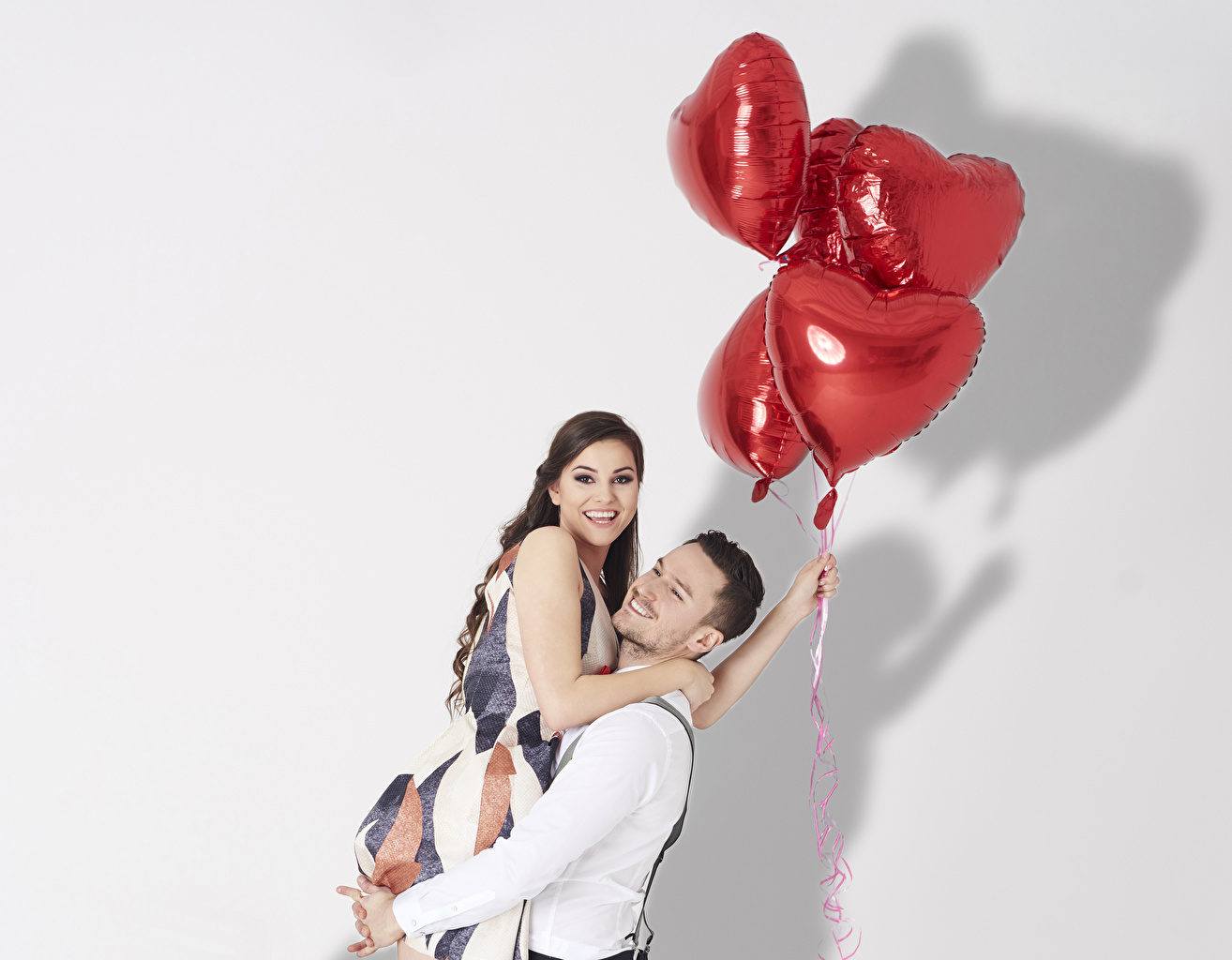 Pictures Valentine's Day Brown haired Man Smile Heart Toy balloon Two Love embrace young woman White background Men balloons 2 Hug hugs Girls female hugging