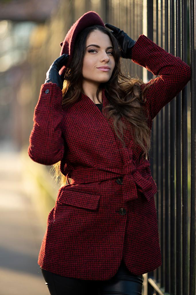 Bilder Bokeh Barett posiert Mantel Mädchens Hand Starren  für Handy unscharfer Hintergrund Pose junge frau junge Frauen Blick