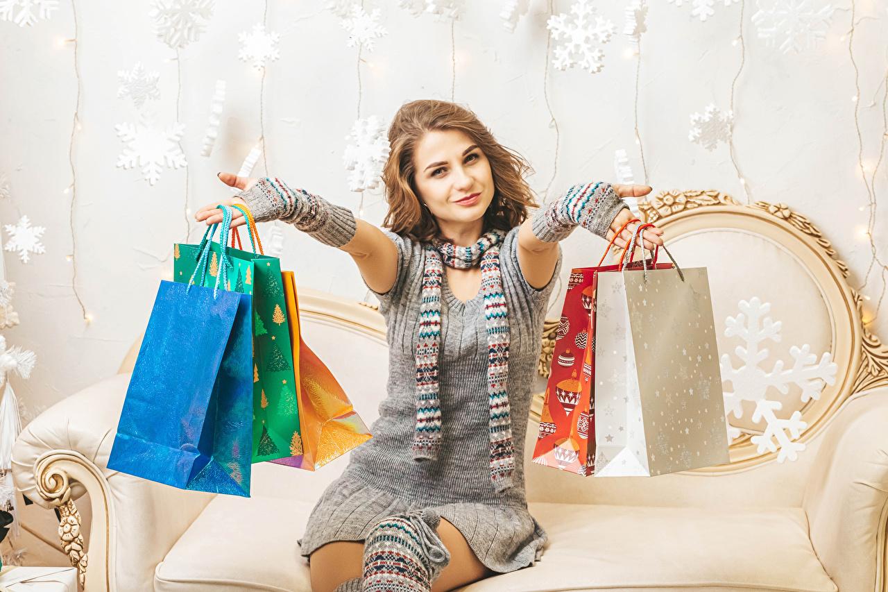 Desktop Hintergrundbilder Neujahr Braunhaarige kaufen Tüte Lächeln junge frau Geschenke Hand sitzt Kleid Braune Haare kaufte kauften Einkaufen Mädchens junge Frauen sitzen Sitzend