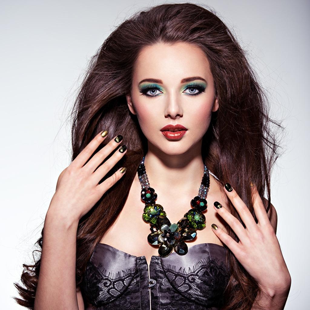 Foto Braunhaarige Maniküre Make Up junge frau Halsketten Hand Starren Grauer Hintergrund Schmuck Braune Haare Schminke Halskette Mädchens junge Frauen Blick