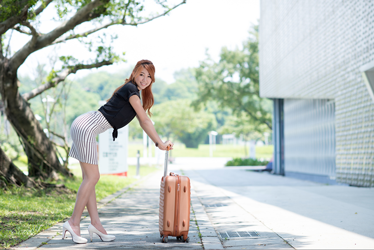 Wallpaper Skirt Brown haired Bokeh Pose young woman Legs Asiatic Suitcase Hands high heels blurred background posing Girls female Asian Stilettos