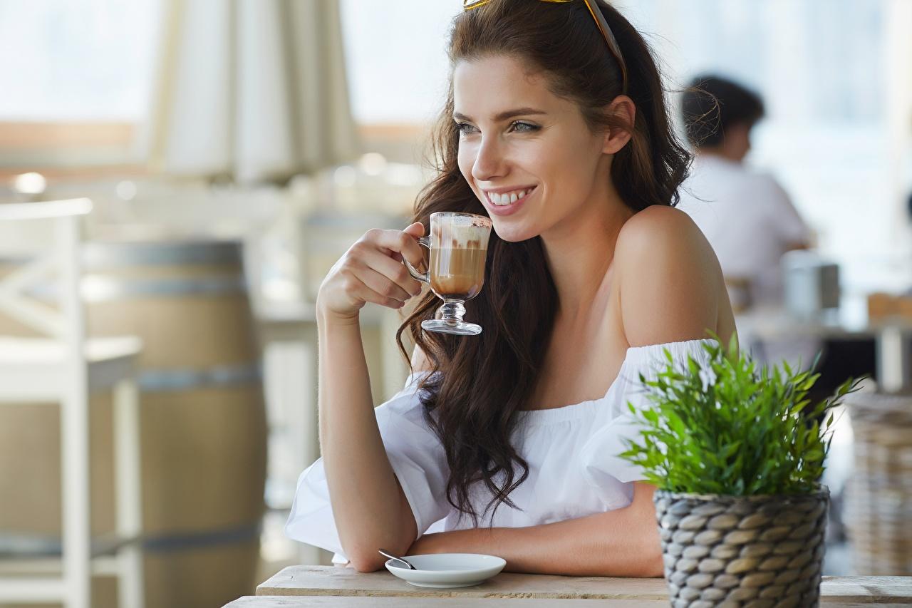 Desktop Hintergrundbilder junge frau Café Braunhaarige Blick Izabela Magier Bokeh Hand Sitzend Lächeln Becher Mädchens junge Frauen Braune Haare Starren unscharfer Hintergrund sitzt sitzen