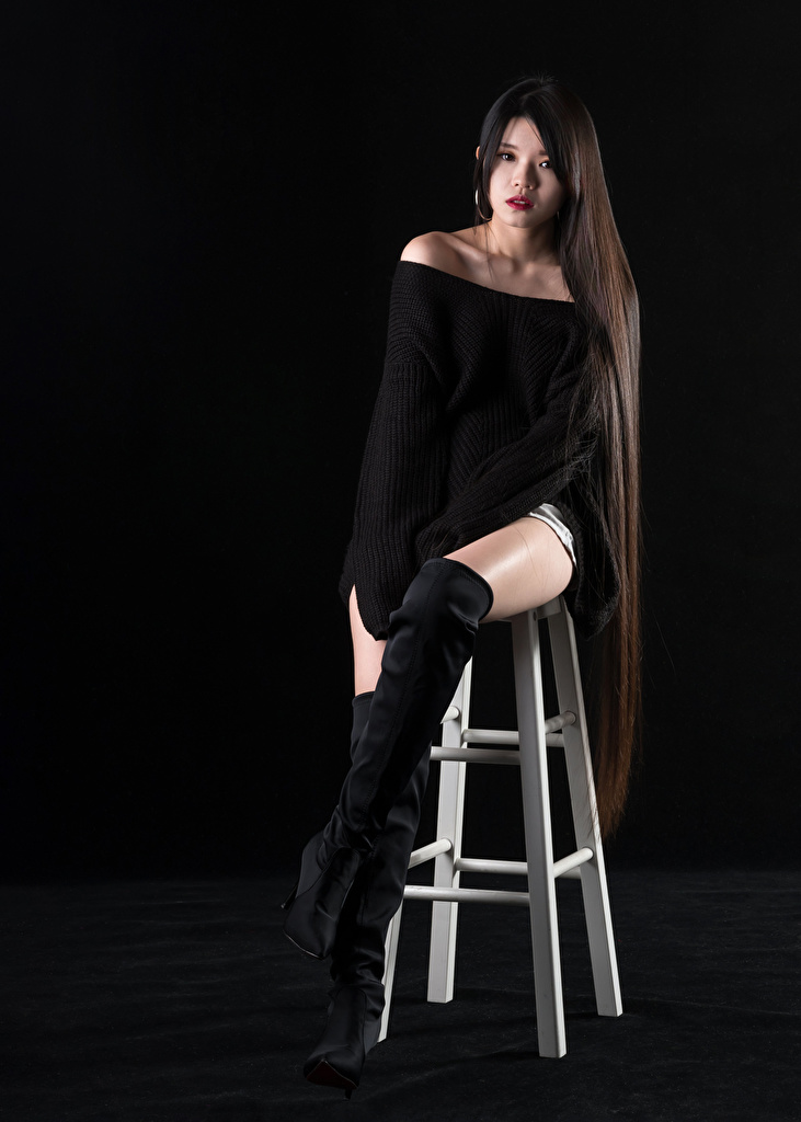Desktop Wallpapers Wearing boots Hair young woman Legs Asian Sweater sit Chair Glance Black background  for Mobile phone Girls female Asiatic Chairs Sitting Staring