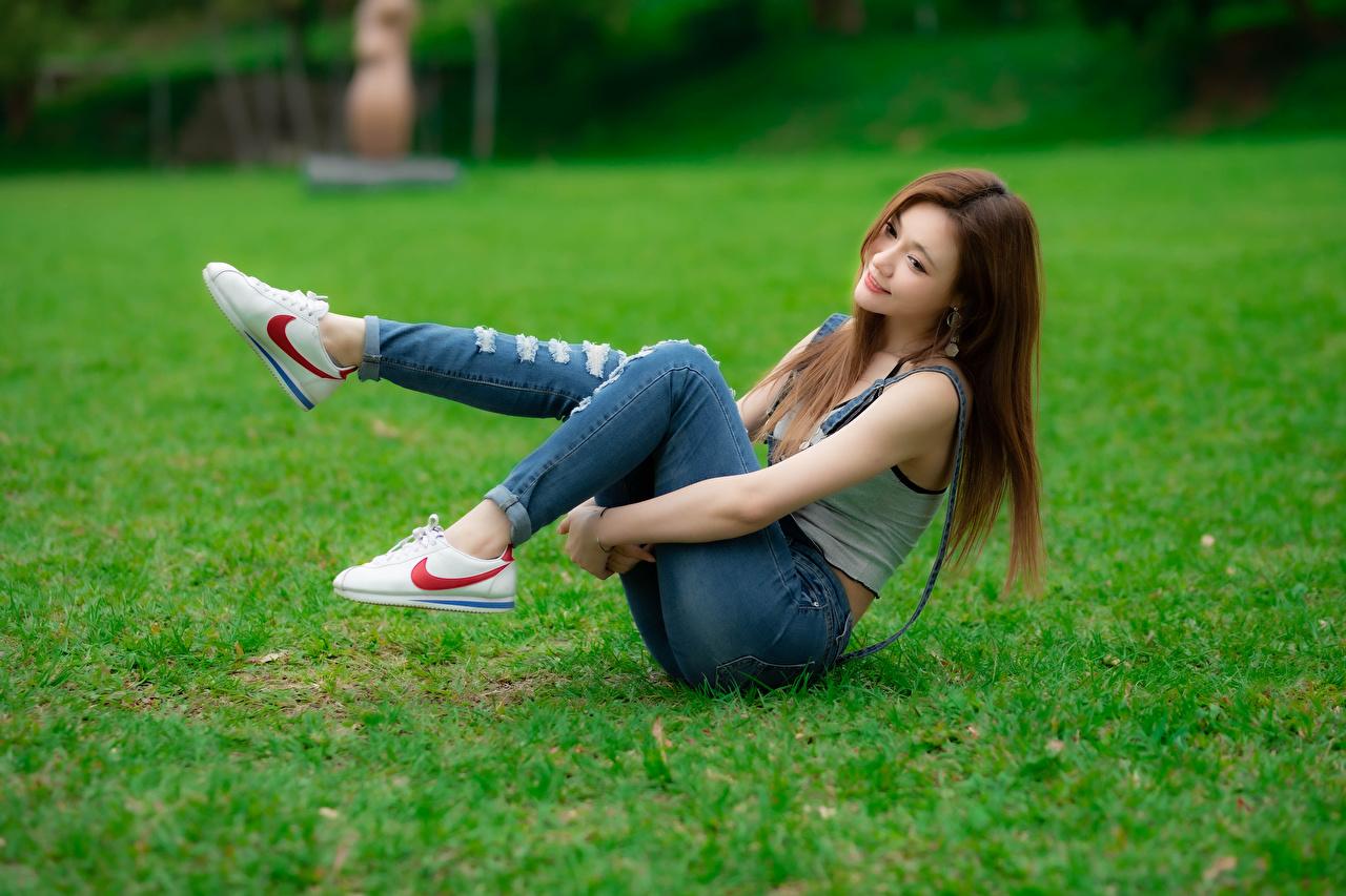 Fotos von unscharfer Hintergrund Mädchens Bein Jeans Asiatische Gras Sitzend Bokeh junge frau junge Frauen Asiaten asiatisches sitzt sitzen