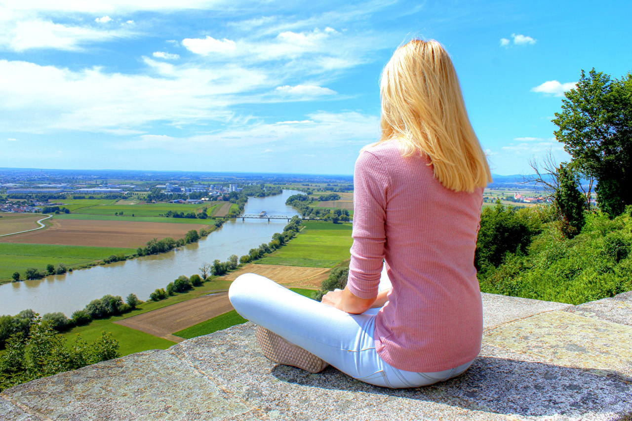 Pictures Lotus position Germany Blonde girl Girls Nature Jeans Fields Sweater river Sitting Padmasana female young woman sit Rivers