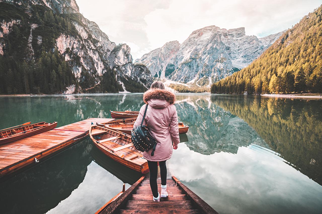 Bilder von Reisender Italien Lake Braies Jacke Gebirge Mädchens See Boot Handtasche Schiffsanleger Tourist Berg junge frau junge Frauen Bootssteg Seebrücke