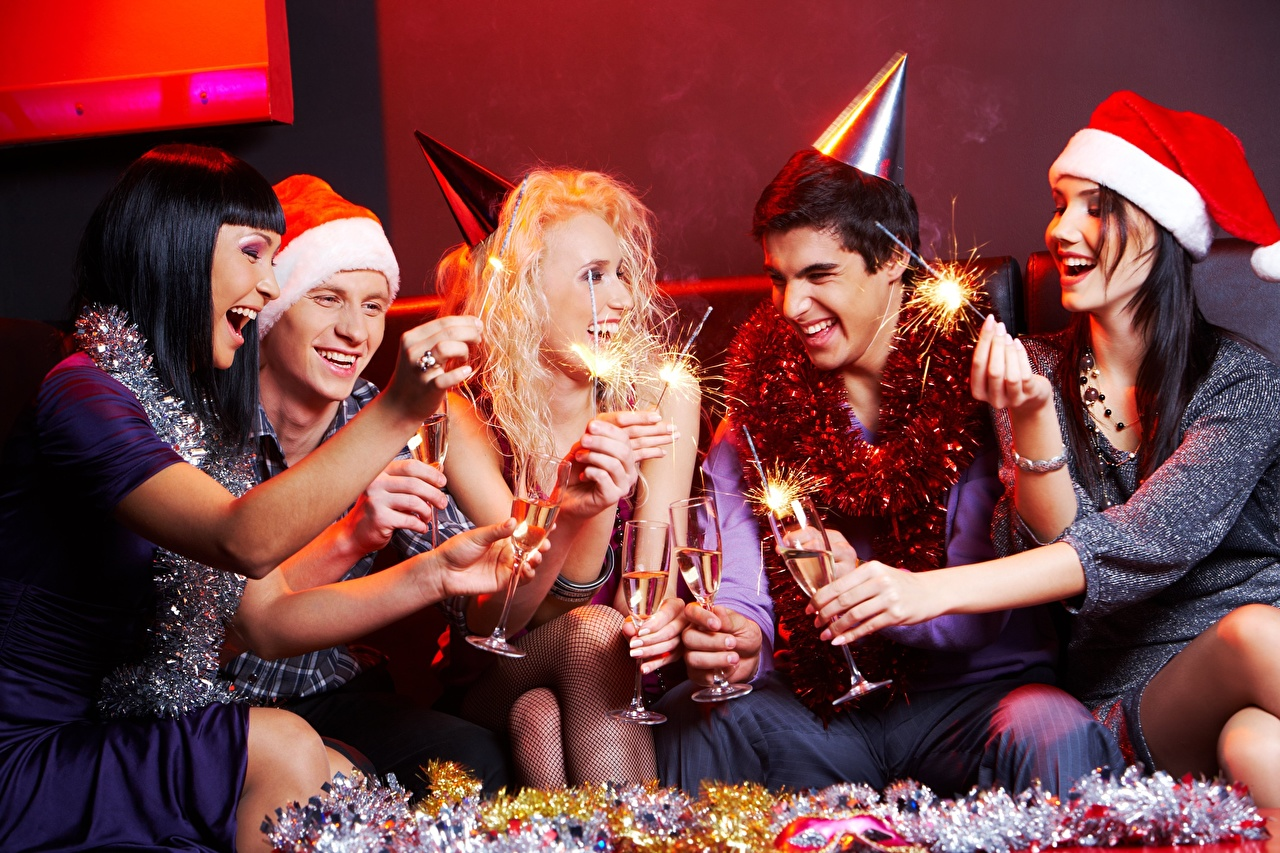 Photos New year Blonde girl Man Sparkler Joy laughs Winter hat young woman Hands Sitting Stemware Christmas Men happy laugh joyful Laughter Girls female sit