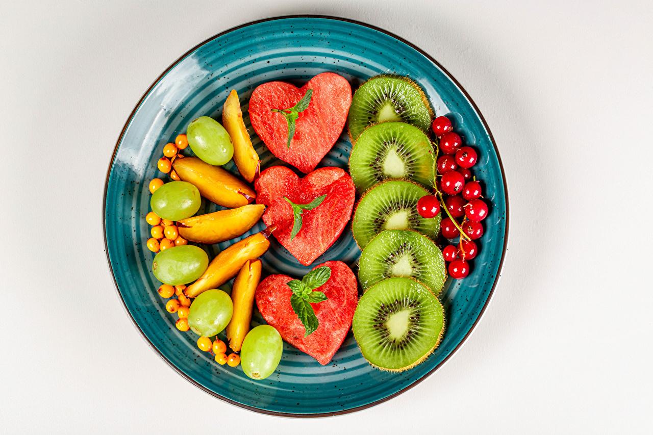 Desktop Hintergrundbilder Herz Kiwifrucht Weintraube Wassermelonen Johannisbeeren Obst Teller das Essen geschnittenes Grauer Hintergrund Kiwi Ribisel Trauben Meertrübeli Chinesische Stachelbeere Geschnitten geschnittene Lebensmittel