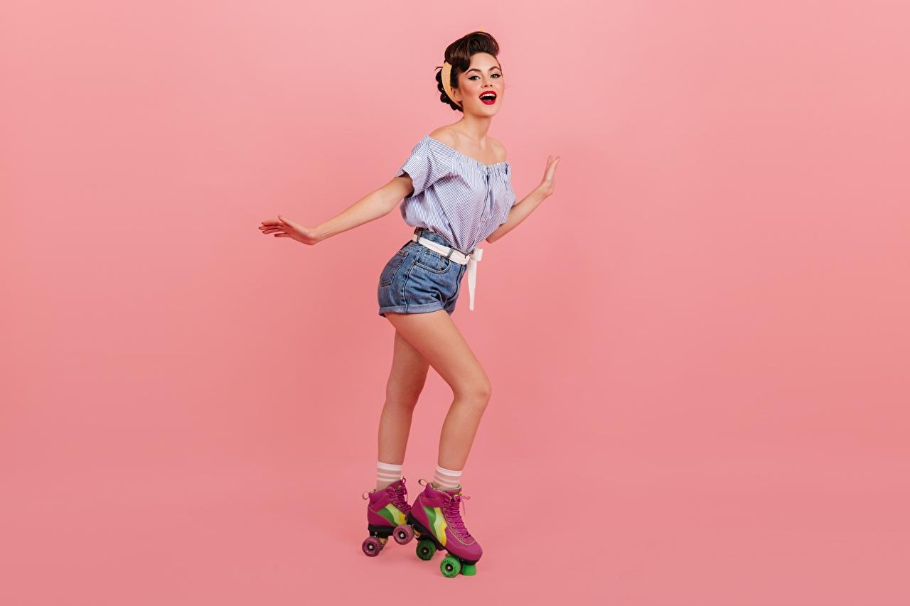 Fotos von Braune Haare Lächeln Bluse Rollschuh Mädchens Bein Shorts Rosa Hintergrund Braunhaarige junge frau junge Frauen