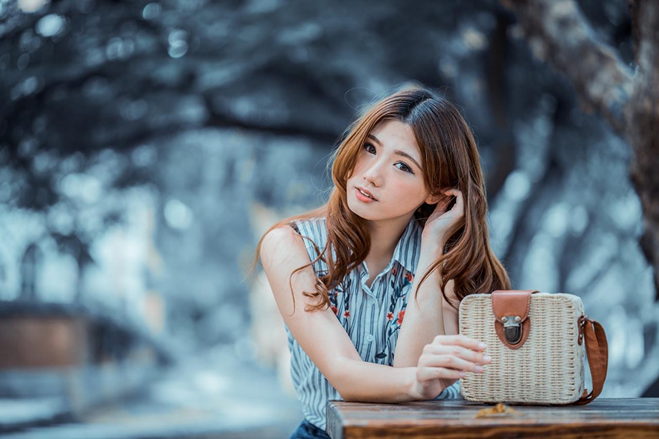 Bilder Braune Haare Bokeh schöne Mädchens Asiaten Hand Handtasche Blick Braunhaarige unscharfer Hintergrund Schön hübsch hübsche schöner schönes hübscher junge frau junge Frauen Asiatische asiatisches Starren
