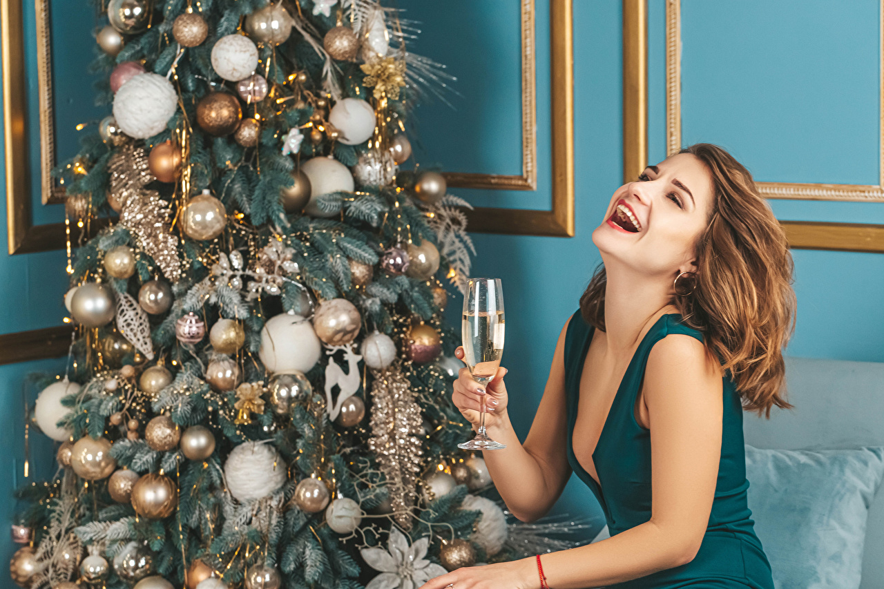 Desktop Wallpapers Christmas Brown haired happy Champagne young woman New Year tree Balls Stemware New year Joy joyful Girls female Sparkling wine Christmas tree