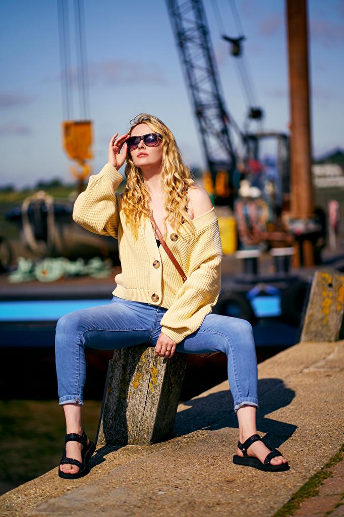 Fotos von Carla Monaco Blond Mädchen unscharfer Hintergrund Pose Mädchens Jeans sitzt Brille  für Handy Blondine Bokeh posiert junge frau junge Frauen sitzen Sitzend