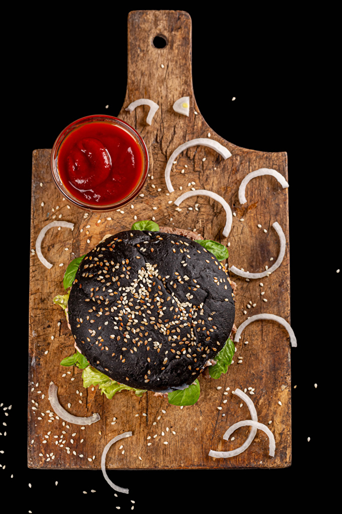 Pictures Black Hamburger Grain Ketchup Fast food Food Cutting board Black background  for Mobile phone