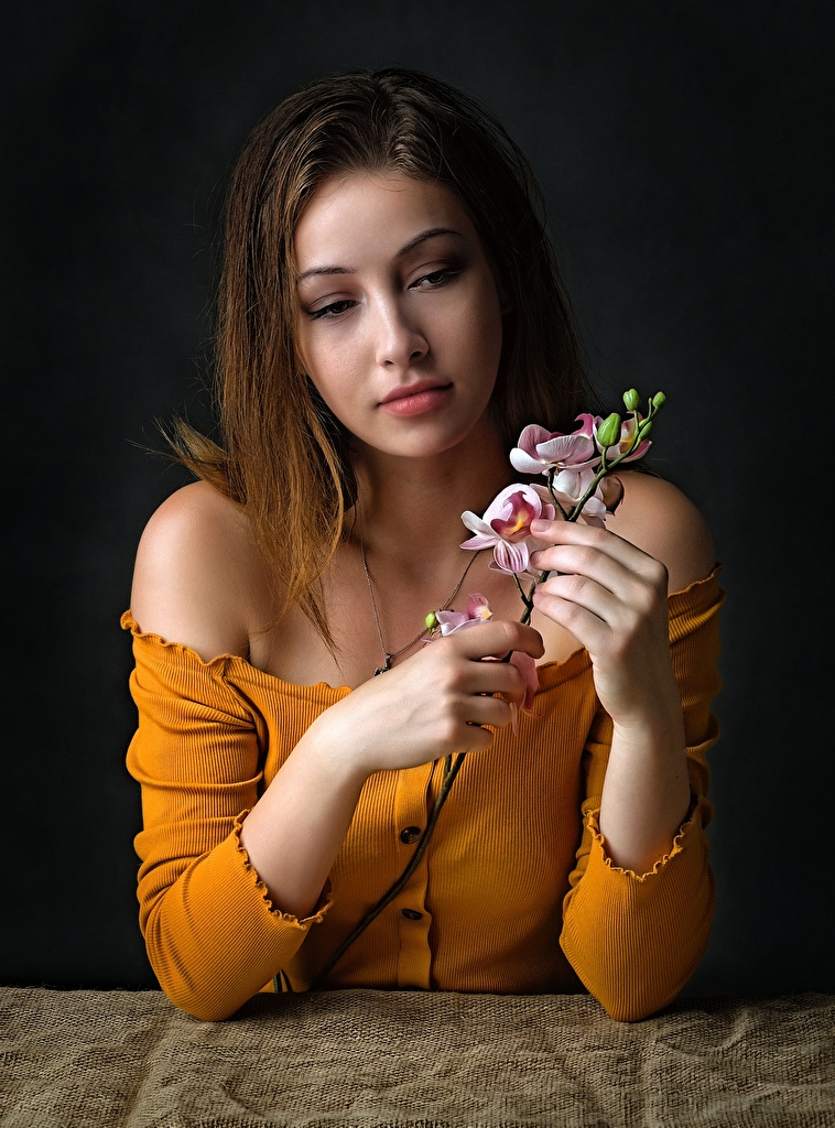 Pictures Brown haired orchids young woman sit Hands Branches  for Mobile phone Girls Orchid female Sitting