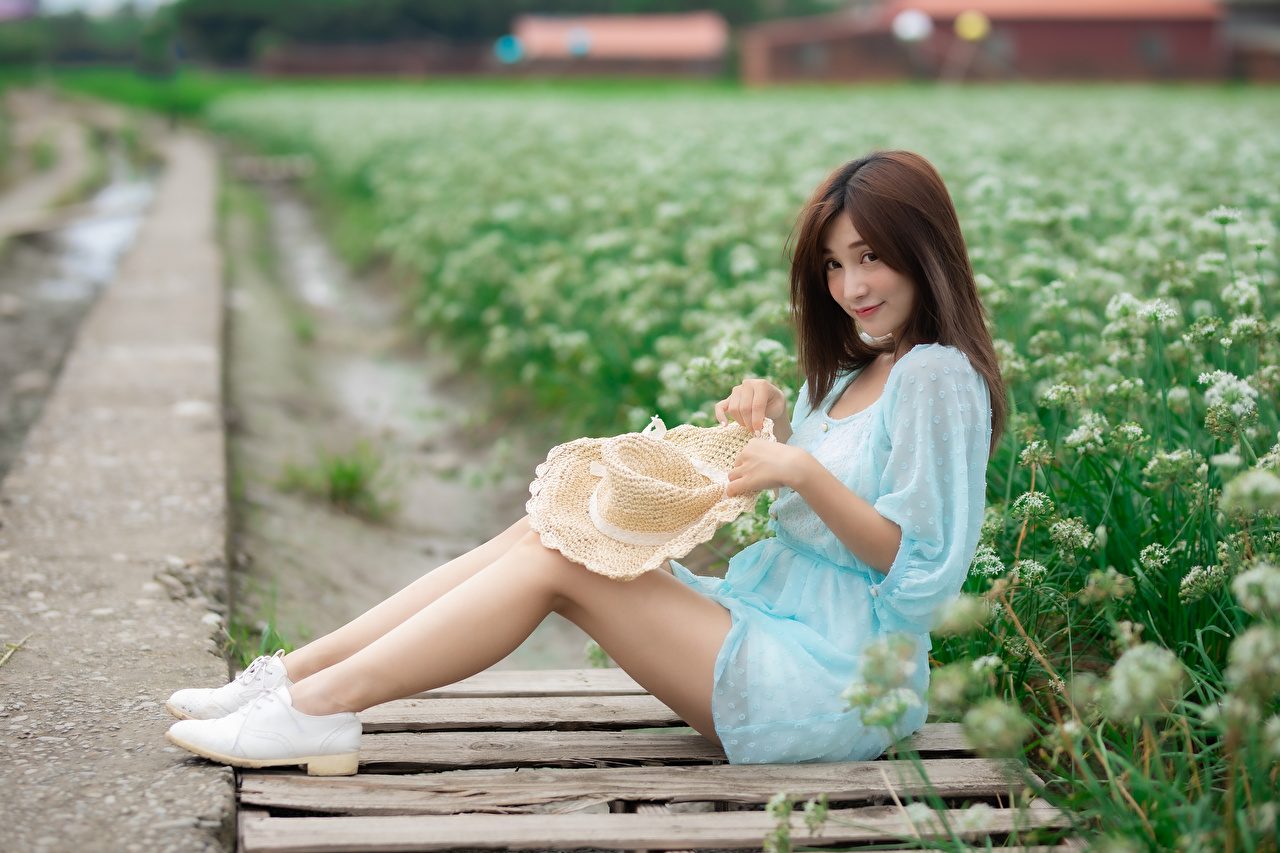 Photos Brown haired Hat female Legs Asian sit Glance Dress Girls young woman Asiatic Sitting Staring gown frock