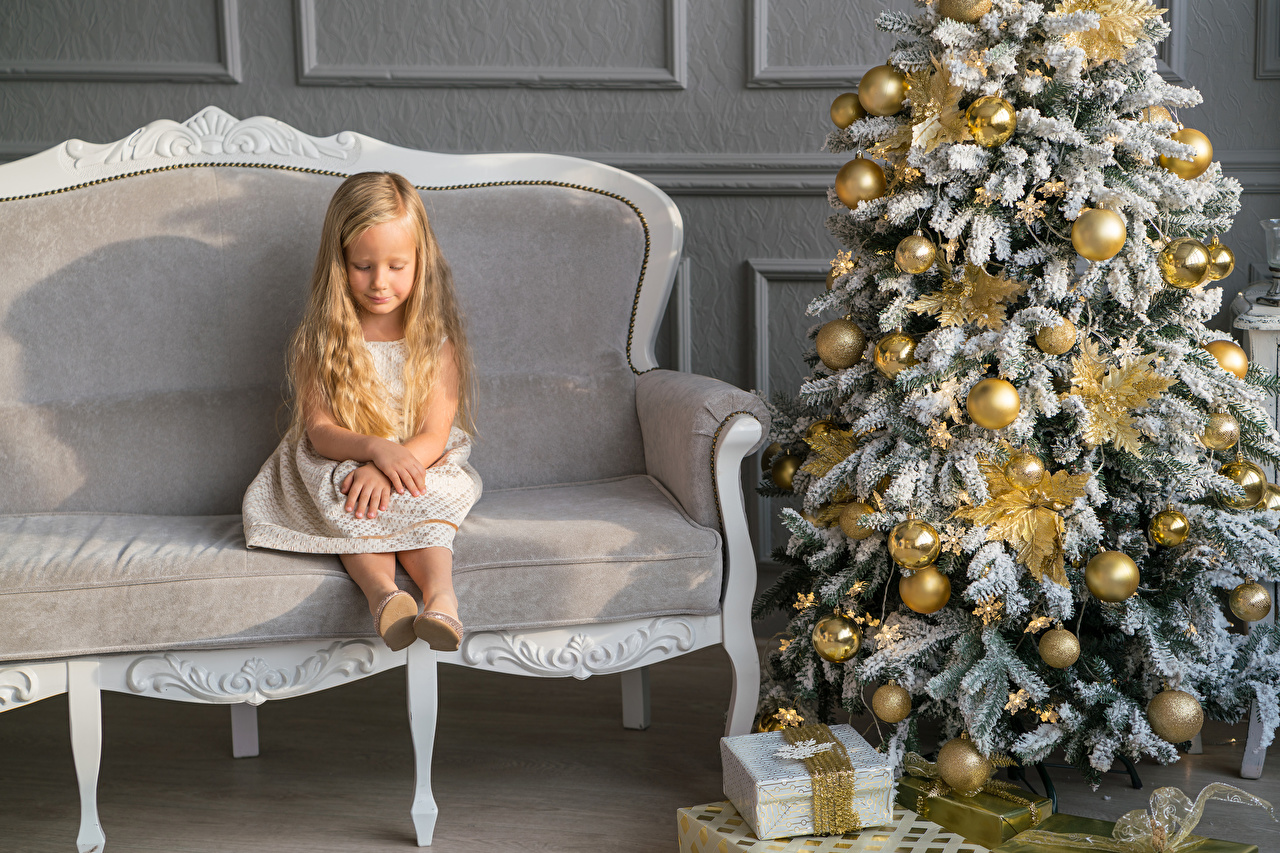 Photo Little girls New year child Christmas tree Gifts Sofa Balls Sitting Holidays Christmas Children New Year tree present sit Couch