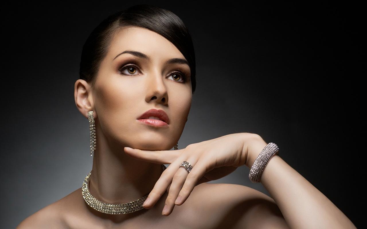Fotos Halskette junge frau Armreif Hand Starren Grauer Hintergrund Schmuck Mädchens Halsketten junge Frauen Armband Blick
