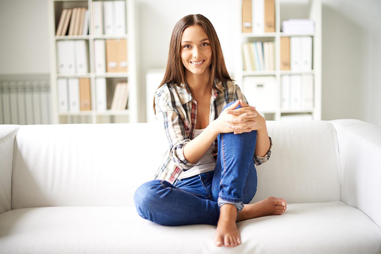 Pictures Brown haired Smile female Formal shirt Legs Jeans sit Sofa Hands Girls young woman Couch Sitting