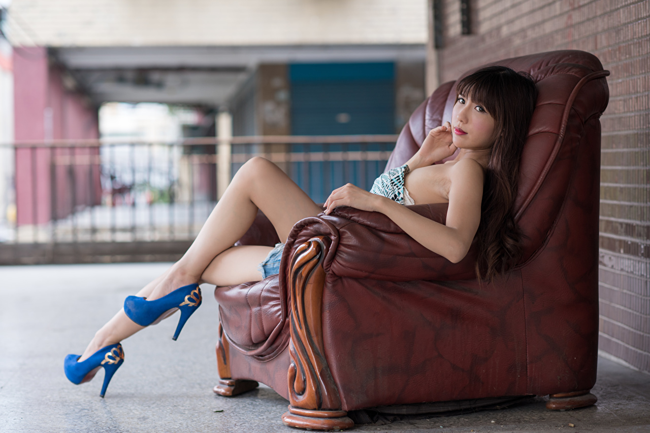 Pictures Brown haired Bokeh Girls Legs Asiatic Hands Sitting Armchair Stilettos blurred background female young woman Asian sit Wing chair high heels