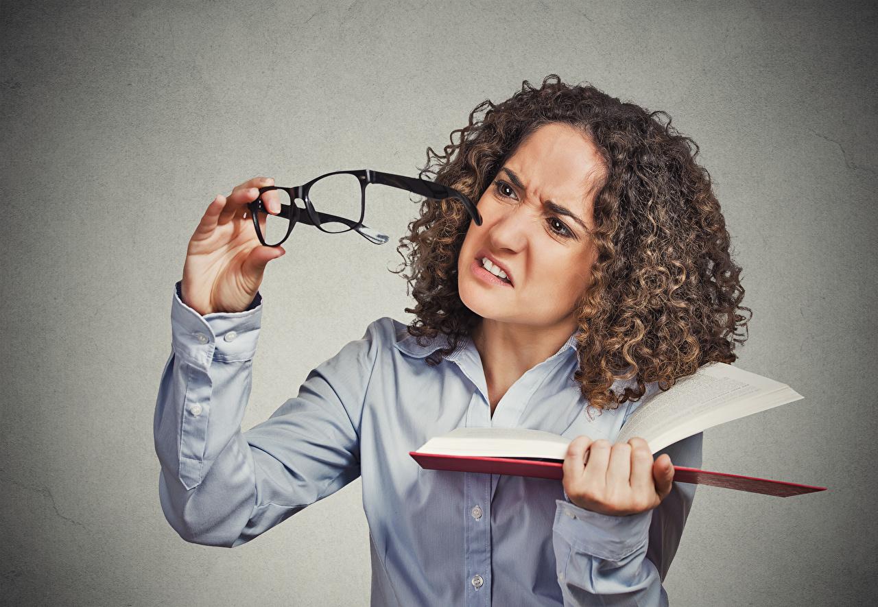 Bilder von Braunhaarige Unzufrieden Lockige Mädchens Hand Buch Brille Grauer Hintergrund Braune Haare missfallen Stirnrunzeln unzufriedene unzufriedener runzelt die Stirn locken junge frau junge Frauen Bücher