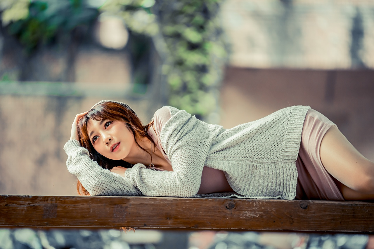 Pictures Brown haired Lying down Bokeh female Sweater Asiatic Glance esting laying blurred background Girls young woman Asian Staring