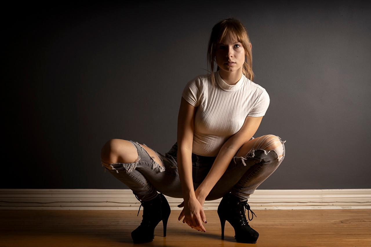 Photos Rebekka Weigand Girls T-shirt Legs Jeans sit Glance high heels female young woman Sitting Staring Stilettos