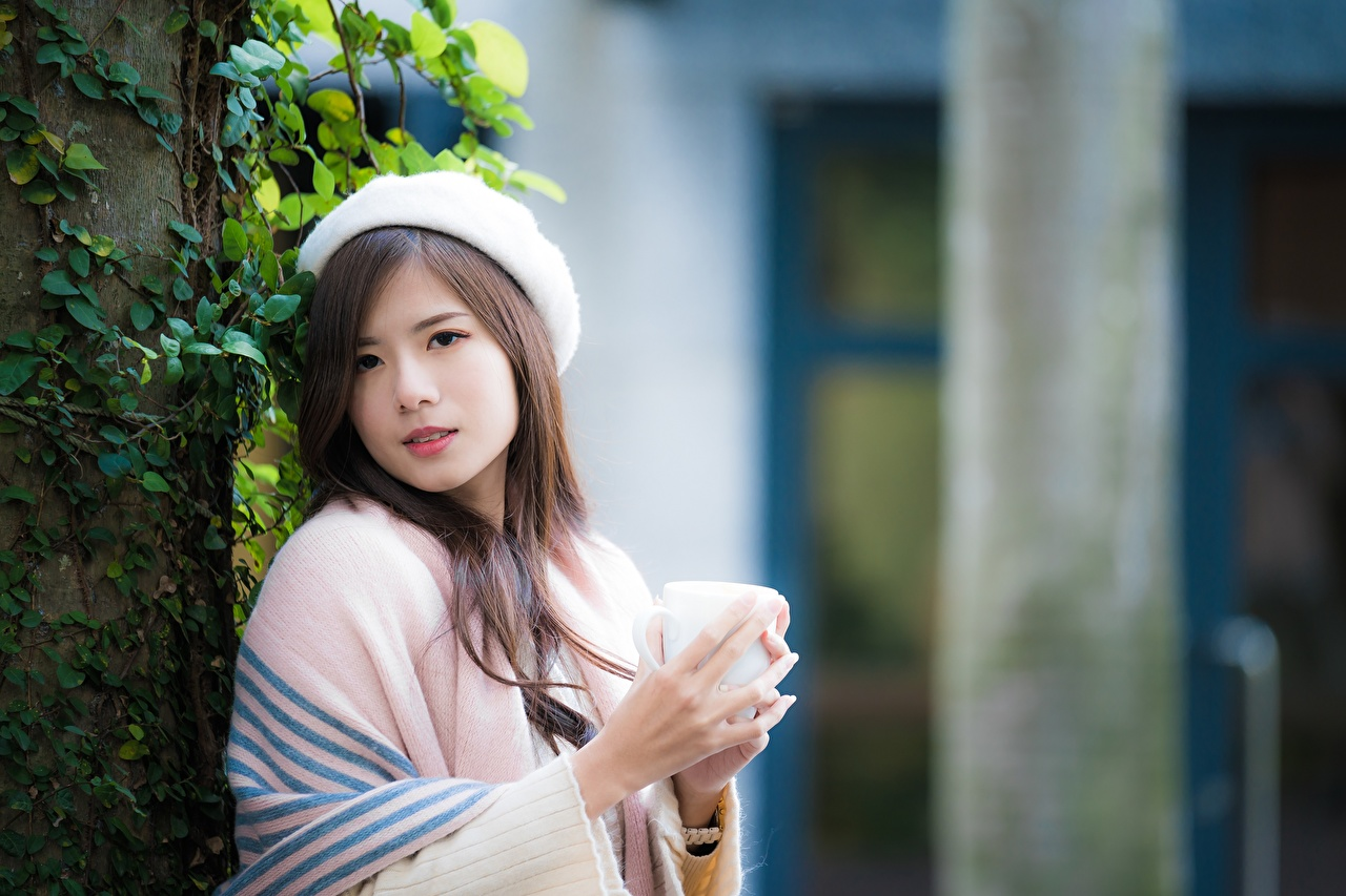 Pictures Brown haired blurred background Beret Girls Asian Mug Hands Glance Bokeh female young woman Asiatic Staring