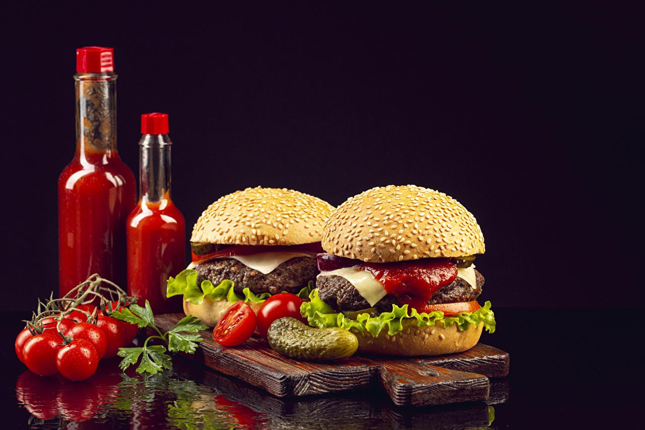 Photo Tomatoes Hamburger Cucumbers Buns Ketchup Food Bottle Cutting board Black background bottles