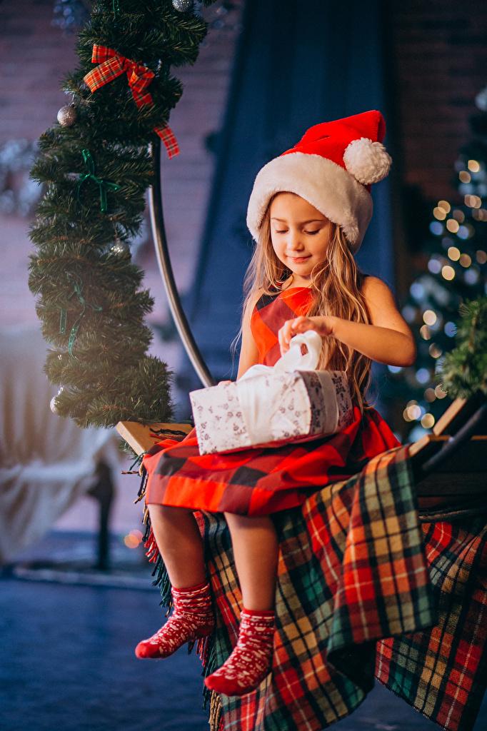 Desktop Hintergrundbilder Kleine Mädchen Neujahr Kinder Mütze Geschenke Ast Sitzend  für Handy kind sitzt sitzen