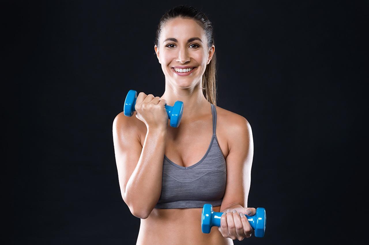 Fotos von Lächeln Fitness Hantel junge frau sportliches Schwarzer Hintergrund Sport Hanteln Mädchens junge Frauen