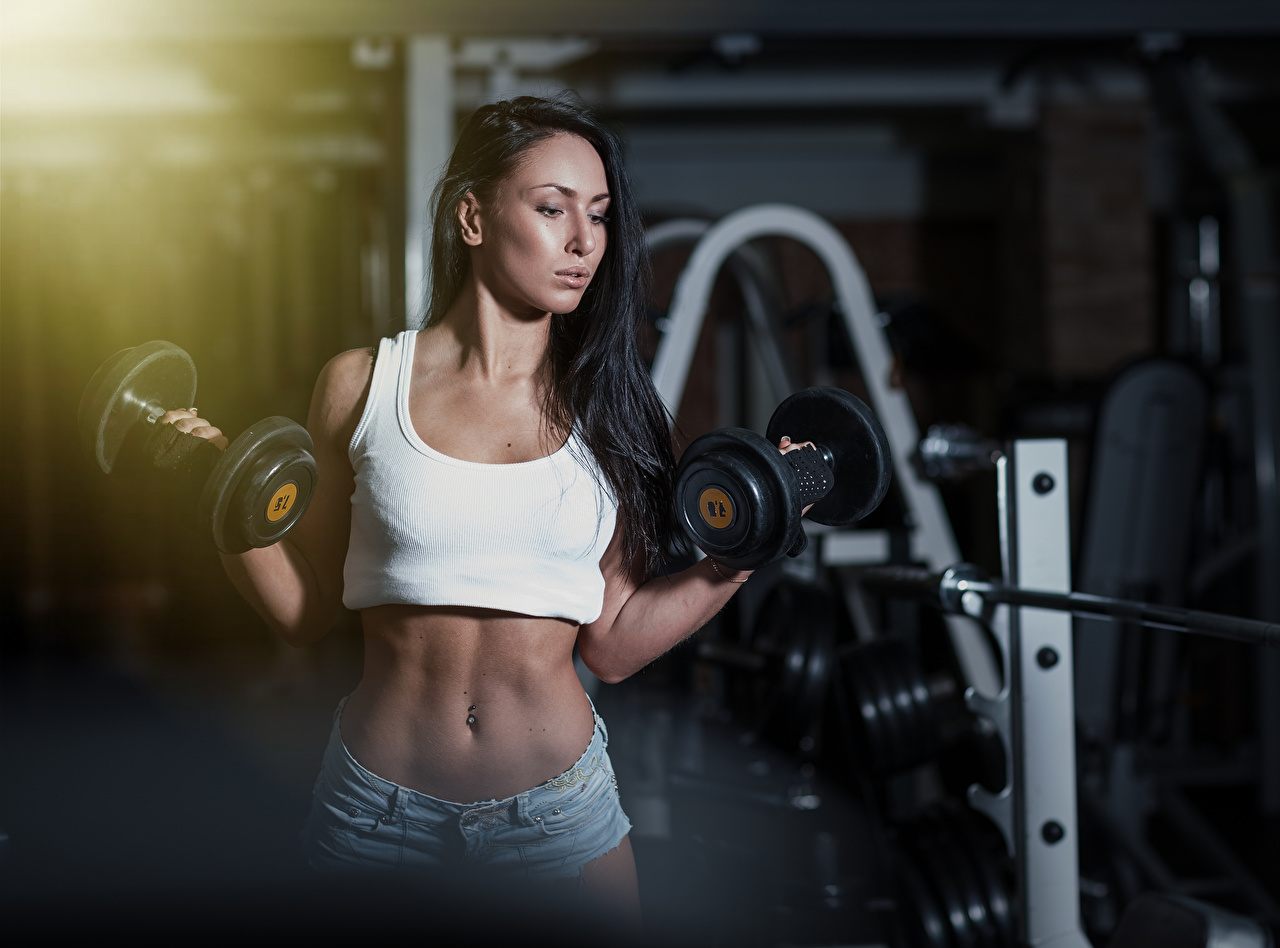 Photo Brunette girl Bokeh Fitness Girls Dumbbells Belly Hands Shorts blurred background female dumbbell young woman