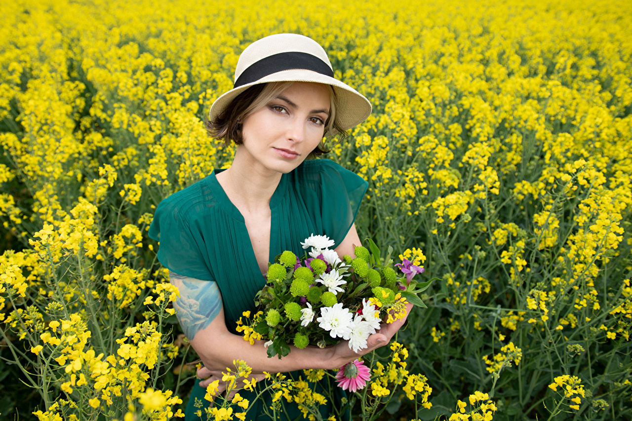 Photo Alena Bouquets Hat female Nature oilseed rape Fields Staring frock bouquet Girls Rapeseed young woman Glance gown Dress