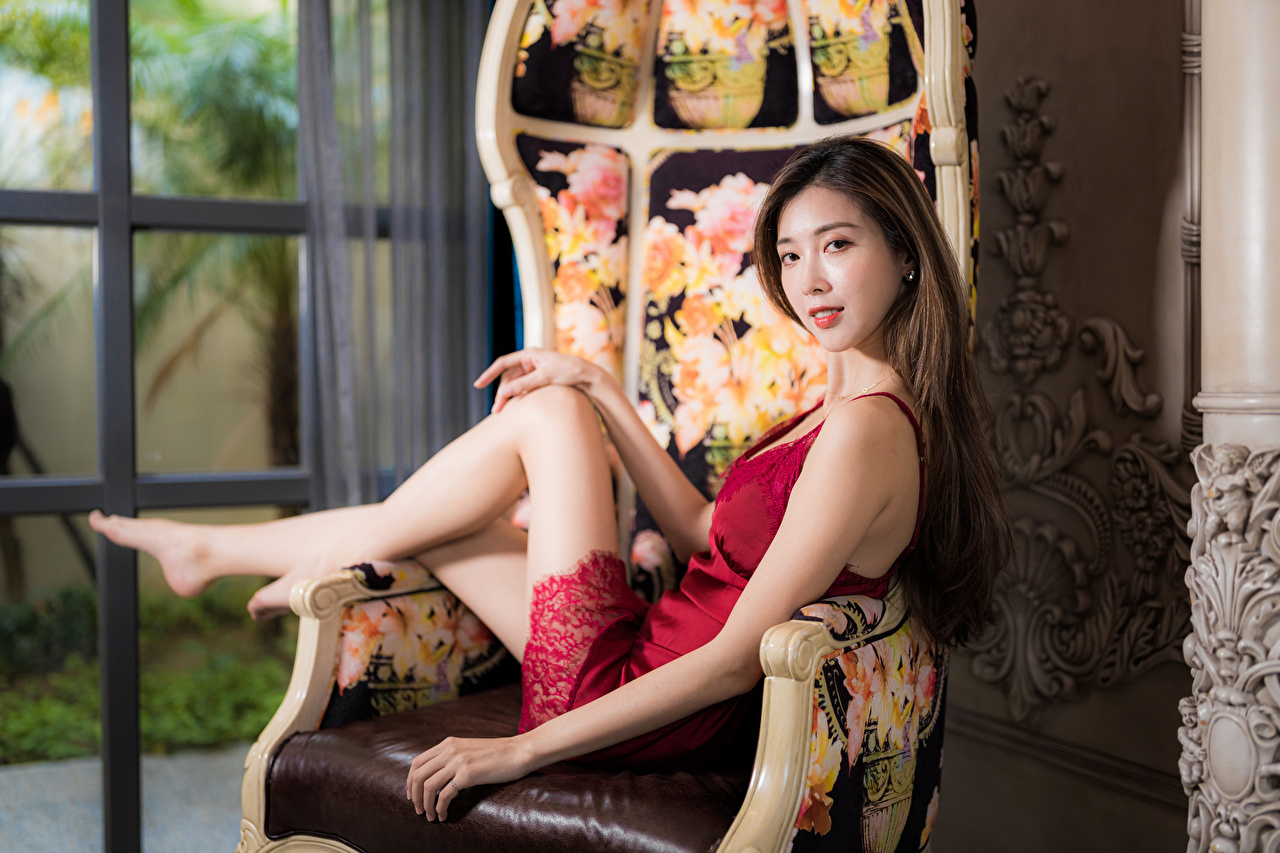 Photos Bokeh young woman Asian Wing chair Staring Dress blurred background Girls female Asiatic Armchair Glance gown frock